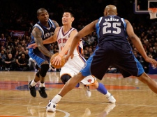 New York Knicks' Jeremy Lin, center, drives through Dallas Mavericks' Vince Carter, right, and Dominique Jones during the first half of an NBA basketball game in New York, Sunday, Feb. 19, 2012. (AP Photo/Seth Wenig)