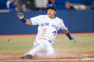 Toronto Blue Jays' Munenori Kawasaki slides into home plate to score against the Seattle Mariners during eighth inning American League baseball action in Toronto on Wednesday, Sept. 24, 2014. (The Canadian Press/Chris Young)