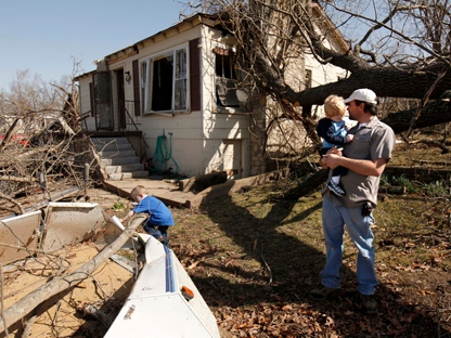 Rob Turpen of Hollister, Mo., holds his son Izaiha, 2, while his son Patrick, 3, climbs over debris at a friend's storm-damaged house just east of Branson, Mo., Wednesday, Feb. 29, 2012. (AP Photo/Mark Schiefelbein)