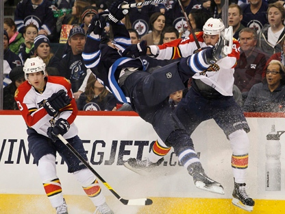 Florida Panthers' Erik Gudbranson, right, takes out Winnipeg Jets' Blake Wheeler during an NHL game in Winnipeg on Thursday, March 1, 2012. (THE CANADIAN PRESS/John Woods)