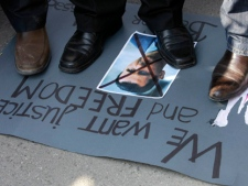 Protesters stand on a crossed out picture of Syrian President Bashar Assad during a rally against his regime in front of the Syrian embassy in Belgrade, Serbia, Tuesday, March 6, 2012. (AP Photo/Darko Vojinovic)