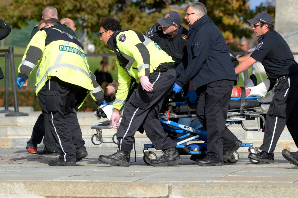 Paramedics and police pull a shooting victim away from the Canadian War Memorial in Ottawa on Wednesday Oct.22, 2014. A Canadian soldier standing guard at the National War Memorial in Ottawa has been shot by an unknown gunman and there are reports of gunfire inside the halls of Parliament. THE CANADIAN PRESS/Adrian Wyld