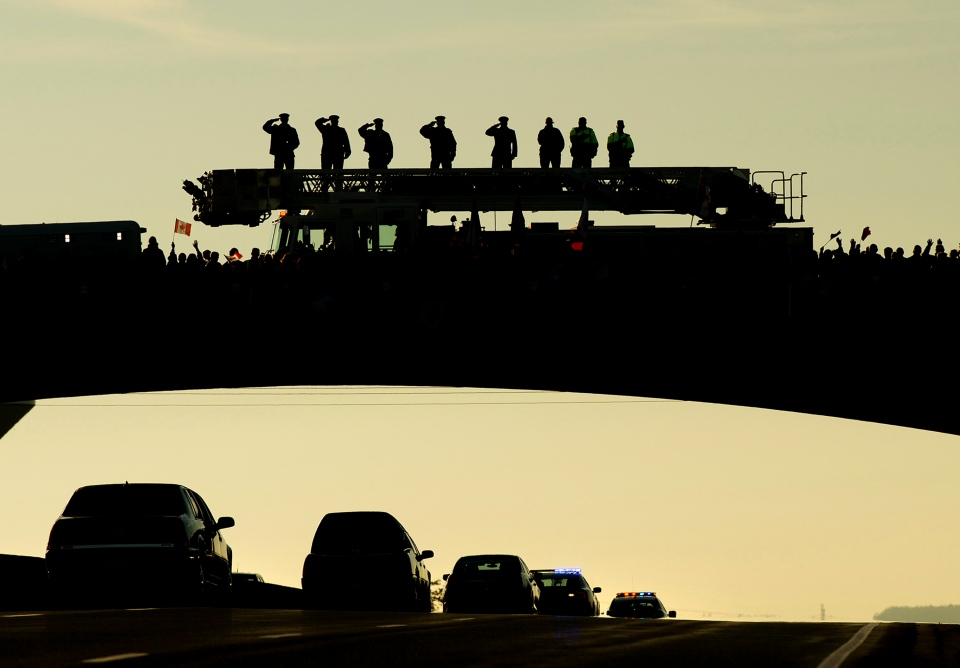 Supporters pay tribute as the body of Cpl. Nathan Cirillo is transported in a hearse from Ottawa to Hamilton, along the Highway of Heroes in Port Hope, Ont., on Friday, Oct. 24, 2014. (The Canadian Press/Nathan Denette)