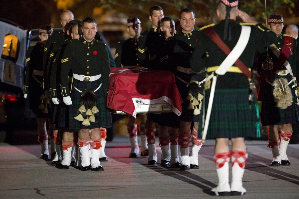 The body of Cpl. Nathan Cirillo is carried by his fellow soldiers into the Dermody-Markey Funeral Home in Hamilton, Ont., on Friday, Oct. 24, 2014. (Peter Power / The Canadian Press)
