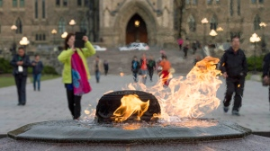 Visitors walk past the Centennial Flame on Parliament Hill in Ottawa, Ontario. (Justin Tang / THE CANADIAN PRESS)