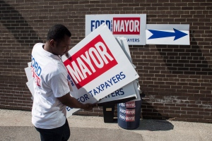 A volunteer carries sign boards outside the campaign offices before Toronto mayoral candidate Doug Ford starts his campaign by door knocking in his local Etobicoke neighbourhood of Toronto on Saturday, September 20, 2014. THE CANADIAN PRESS/Chris Young