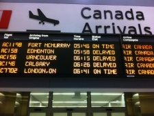 An arrivals board shows delayed flights at Pearson International Airport's Terminal 1 early Friday, March 23, 2012, after Air Canada baggage handlers began staging a wildcat strike at the airport. (CP24/Tom Stefanac)