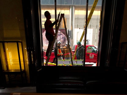 Andrew Joel Smith climbs up a ladder to put the finishing touches on some caulking in the lobby of the Trump International Hotel in Toronto on Monday January 30, 2012. THE CANADIAN PRESS/Frank Gunn