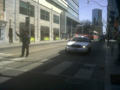 A Toronto police officer directs traffic on Queen Street West at St. Patrick Street on Monday, March 26, 2012. A stretch of Queen Street West was closed after glass reportedly fell from a building. (CP24/Chris Kitching)