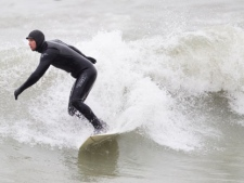 A surfer rides the waves on Lake Ontario at the Scarborough Bluffs on March 31, 2012. (Sandie Benitah/CP24)