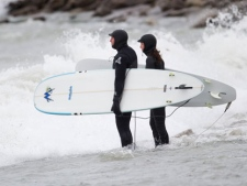 Two surfers assess the conditions before jumping into Lake Ontario at the Scarborough Bluffs on March 31, 2012. (Sandie Benitah/ CP24)