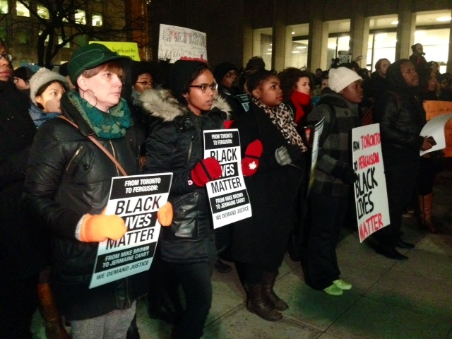 "Demonstrators hold signs at the ""Black Lives Matter"" protest outside the U.S. Consulate in Toronto on Tuesday, Nov. 25, 2014. (CP24/Cristina Tenaglia)"