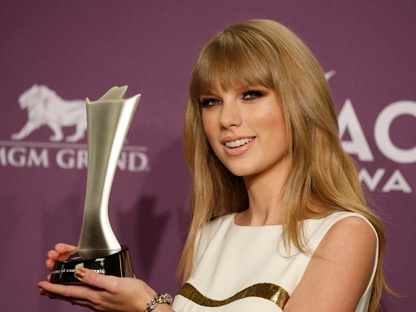 Taylor Swift poses backstage with the award for entertainer of the year at the 47th Annual Academy of Country Music Awards on Sunday, April 1, 2012, in Las Vegas. (AP Photo/Isaac Brekken)