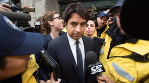 Former CBC Radio host Jian Ghomeshi, centre, is escorted by police out of court past members of the media in Toronto on Wednesday, November 26, 2014. THE CANADIAN PRESS/Darren Calabrese