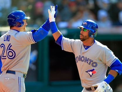 Toronto Blue Jays' Jose Bautista is greeted by Adam Lind (26) after Bautista's solo home run off Cleveland Indians starting pitcher Justin Masterson in the fourth inning of an opening day baseball game on Thursday, April 5, 2012, in Cleveland. (AP Photo/Mark Duncan)