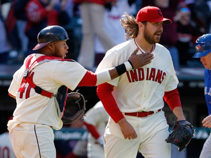 Cleveland Indians catcher Carlos Santana congratulates relief pitcher Chris Perez after he got Toronto Blue Jays' Jose Bautista to fly out for the final out in the Indians' 4-3 win in a baseball game in Cleveland on Sunday, April 8, 2012. (AP Photo/Amy Sancetta)
