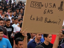 Bahraini anti-government protesters in Bilad al-Qadeem, Bahrain, on the edge of the capital of Manama, march toward the nearby U.S. Embassy on Tuesday, April 10, 2012. The sign refers to U.S.-made tear gas canisters that have been used heavily by riot police during the unrest. (AP Photo/Hasan Jamali)