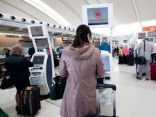 "People check in at Toronto's Pearson airport on Friday, April 13, 2012. Air Canada says an ""illegal job action"" by some of its pilots caused cancellations and delays across the country. (THE CANADIAN PRESS/Michelle Siu)"
