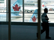"A person walks by Air Canada planes at Toronto's Pearson airport Friday, April 13, 2012. Air Canada says an ""illegal job action"" by some of its pilots caused cancellations and delays across the country. (THE CANADIAN PRESS/Michelle Siu)"