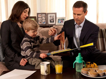 Ontario Premier Dalton McGuinty reads a books with two-and-a-half-year-old Rowan Henderson as his mother Naomi looks on in Ottawa on Friday, March 30, 2012. (THE CANADIAN PRESS/Adrian Wyld)