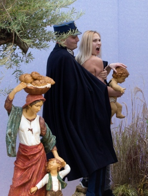 A Vatican police officer stops a Ukrainian feminist group Femen activist after she snatched the statue of Baby Jesus from the Nativity scene set in St. Peter's Square at the Vatican, Thursday, Dec. 25, 2014. (AP Photo)