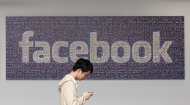In this June 11, 2014 photo, a man walks past a Facebook sign in an office on the Facebook campus in Menlo Park, Calif. (AP/Jeff Chiu)