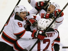 New Jersey Devils' Zach Parise (9), Alexei Poonikarovsky (12), Marek Zidlicky (2) and David Clarkson, top right, mob Adam Henrique, obscured, after he scored during the second overtime against the Florida Panthers in Game 7 of a first-round NHL Stanley Cup playoff hockey series in Sunrise, Fla., Wednesday, April 26, 2012. The Devils won 3-2. (AP Photo/J Pat Carter)