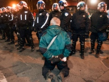 A man kneels in front of riot police as students protest against tuition fee hikes Friday, April 27, 2012 in Montreal.THE CANADIAN PRESS/Ryan Remiorz