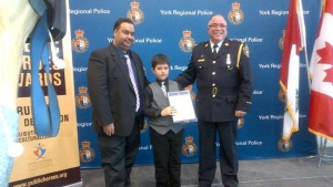 Six-year-old Arjunpal Khattra receives an award for bravery from York Regional Police Monday January 12, 2015. (York Regional Police)