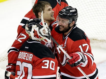 New Jersey Devils' Alexei Ponikarovsky, top, of Ukraine, celebrates his game-winning goal against the Philadelphia Flyers with teammates Ilya Kovalchuk (17), of Russia, and Martin Brodeur (30) in a 4-3 overtime victory in Game 3 of a second-round NHL hockey Stanley Cup playoff series on Thursday, May 3, 2012 in Newark, N.J. The Devils took a 2-1 lead in the series. (AP Photo/Julio Cortez)