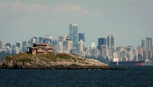 Downtown Vancouver is seen in the background as a house sits on top of a small island in West Vancouver, B.C., on June 10, 2013. (The Canadian Press/Jonathan Hayward)