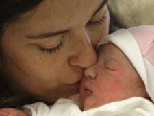 Alex Taylor kisses her newborn daughter in this file photo. (THE CANADIAN PRESS/Darryl Dyck)
