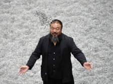 In this Monday, Oct. 11, 2010 file photo Chinese artist Ai Weiwei poses with some seeds from his art installation 'Sunflower Seeds' in London. (AP Photo/Lennart Preiss)