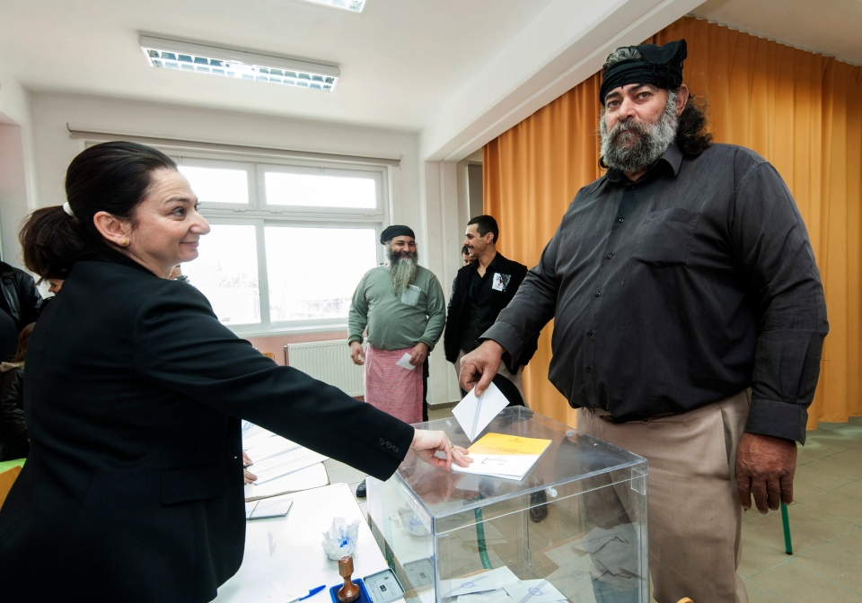 A man with a traditional Cretan costume casts his vote at a polling station in Kyparissi village, on the southern Greek island of Crete, Sunday, Jan. 25, 2015. Greeks were voting Sunday in an early general election crucial for the country's financial future, with the radical left Syriza party of Alexis Tsipras tipped as the favorite to win, although possibly without a large enough majority to form a government. (AP Photo/Bastian Parschau)