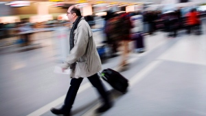 A man carries his luggage at Pearson International Airport in Toronto on December 20, 2013. (Mark Blinch/THE CANADIAN PRESS)