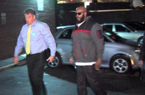 "This image from video shows Death Row Records founder Marion ""Suge"" Knight, right, walking into the Los Angeles County Sheriffs department early Friday morning Jan. 30, 2015 in connection with a hit-and-run incident that left one man dead and another injured. Man at left is an unidentified police officer. (AP /OnSceneVideo via AP Television)"
