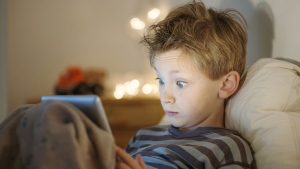 Child with a tablet computer. (Jack Frog / shutterstock.com)