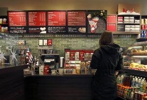 A Starbucks customer orders at a Chicago area store Wednesday, Dec. 5, 2012. (AP Photo/Charles Rex Arbogast)