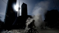Stream rises from the street as a cyclist makes their way around in the below normal cold weather in Toronto on Friday, Feb. 13, 2015. (Nathan Denette / THE CANADIAN PRESS)