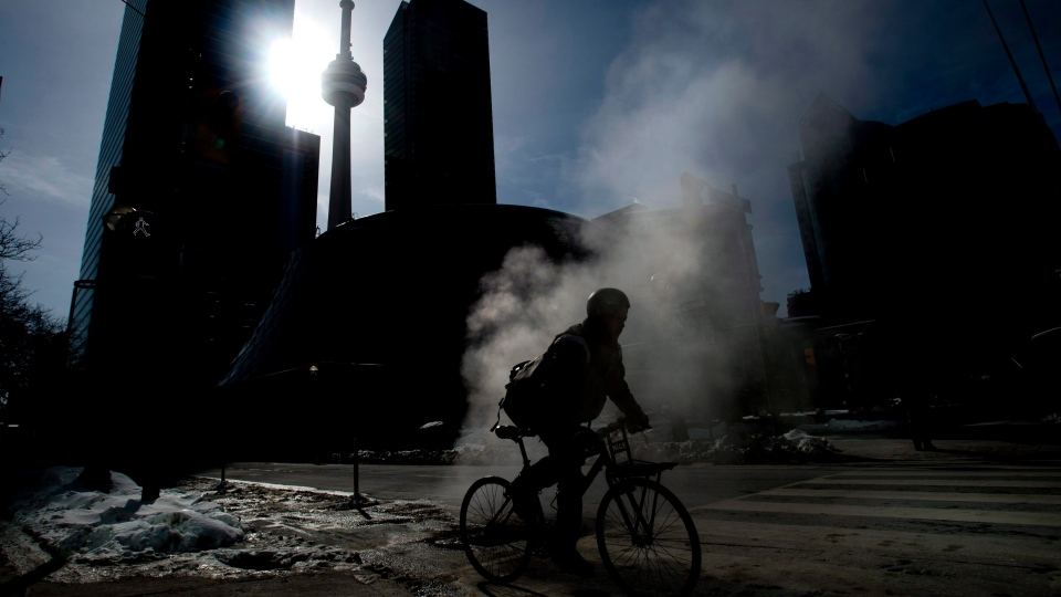 Steam rises from the street as a cyclist makes their way around Toronto on Friday, February 13, 2015. (Nathan Denette/THE CANADIAN PRESS)