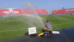 A member of the grounds crew waters the field just before the Tottenham Hotspur Football Club take part in a practice at BMO Field in Toronto on Tuesday, July 22, 2014. (The Canadian Press/Neil Davidson)