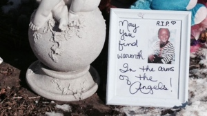 "At a memorial for three-year-old Elijah Marsh, a photo frame holding a picture of toddler reads, ""May you find warmth in the arms of the angels."" (Cam Woolley/ CP24)"