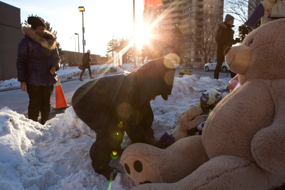 A young boy lays flowers at a memorial for Elijah Marsh on Friday, February 20, 2015. The three-year-old boy died Thursday afternoon after wandering away from his North York home in the early hours of the icy morning dressed only in a T-shirt, boots and a diaper. (Chris Young /The Canadian Press)