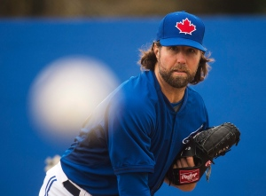 Toronto Blue Jays starting pitcher R.A. Dickey pitches in the bullpen to Blue Jays catcher Russell Martin during baseball spring training in Dunedin, Fla., on Wednesday, February 25, 2015. (Nathan Denette /The Canadian Press)