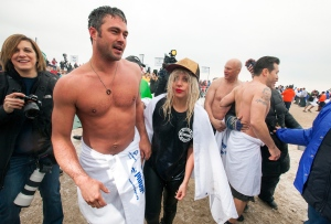 """Actor Taylor Kinney, second left, and his fiancée, pop star Lady Gaga, center, along with """"Chicago Fire"""" cast take part in the Chicago Polar Plunge at North Avenue Beach on Sunday, March 1, 2015 in Chicago. (Barry Brecheisen/Invision/AP)"""