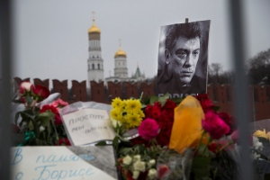 """Flowers and a condolence message that reads """"In memory of Boris"""" are placed with a portrait of Boris Nemtsov, a charismatic Russian opposition leader and sharp critic of President Vladimir Putin, at the site where Nemtsov was gunned down near the Kremlin, against a backdrop of the Kremlin Wall, in Moscow, Russia, Monday, March 2, 2015. Nemtsov was killed on Friday, Feb. 27 in what many in the opposition believe was reprisal for his unrelenting criticism of Putin. No suspects have yet been detained in connection with the killing. (AP Photo/Ivan Sekretarev)"""