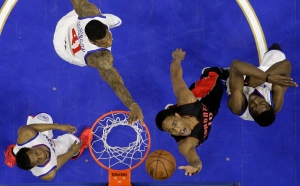 Toronto Raptors' DeMar DeRozan (10) shoots against Philadelphia 76ers' Jerami Grant, from right, Thomas Robinson and Ish Smith during the first half of an NBA basketball game, Monday, March 2, 2015, in Philadelphia. (AP Photo/Matt Slocum)