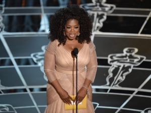 Oprah Winfrey presents the award for best adapted screenplay at the Oscars on Sunday, Feb. 22, 2015, at the Dolby Theatre in Los Angeles. (Photo by John Shearer/Invision/AP)
