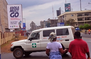 In this photo taken Saturday, Feb. 21, 2015, an ambulance drives past a billboard, left rear, reading 'Ebola most go' in the city of Monrovia, Liberia. Eight health workers at a hospital in Liberia's capital have been sent home for observation after coming into contact with a patient who later tested positive for Ebola, the country's assistant health minister said Saturday. (AP Photo/ Abbas Dulleh)