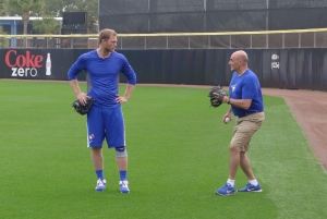 Blue Jays outfielder Michael Saunders, left, chats with head trainer George Poulis after a throwing session in Dunedin, Fla., on Friday, March 6, 2015. Saunders underwent a knee procedure last week after tearing his meniscus in a freak accident when he stepped on a sprinkler head indentation. (Neil Davidson /The Canadian Press)